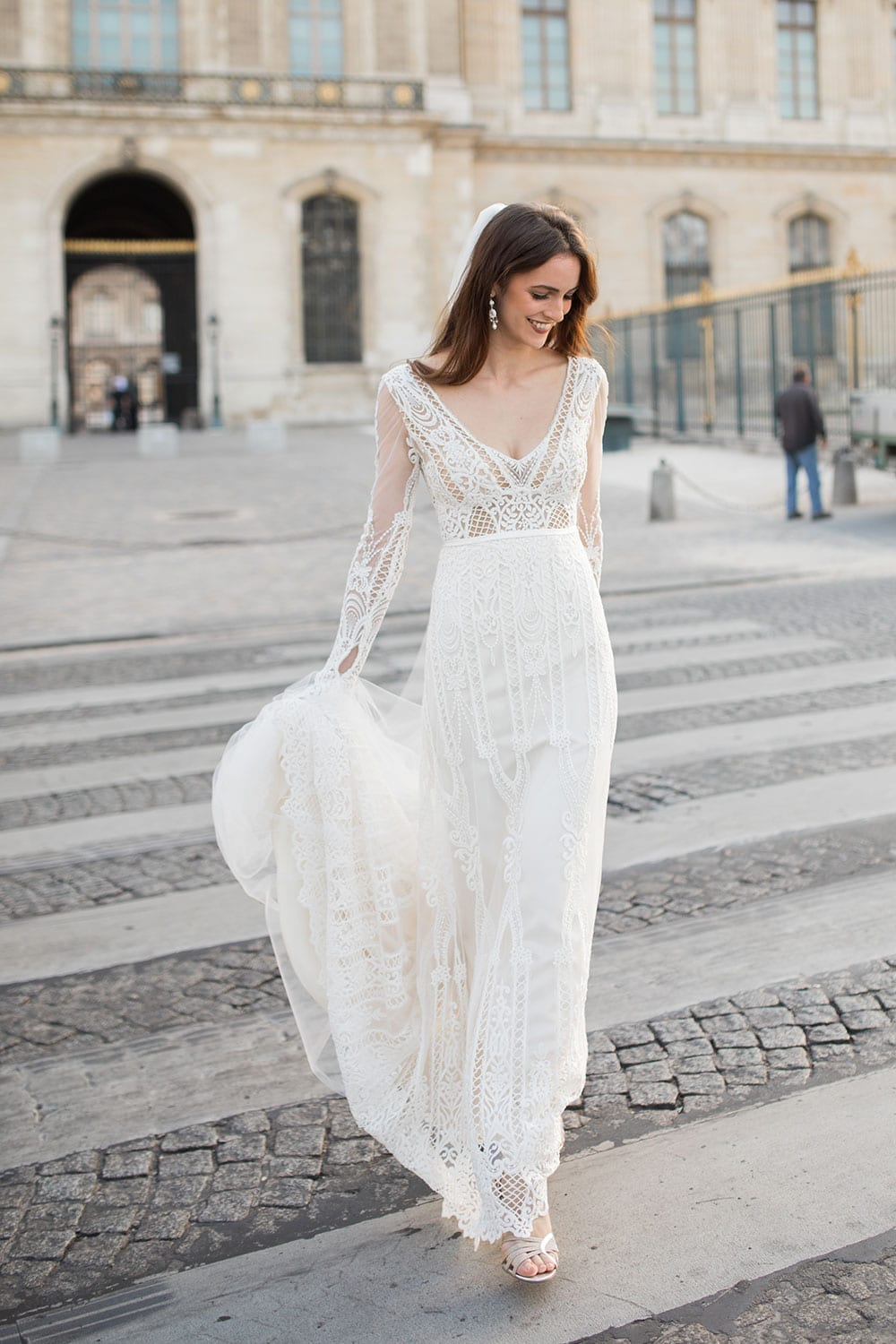 Model wearing Vinka Design Briar Wedding Dress, with gorgeous corded embroidered lace features, a sheer ivory base and long fitted sleeves with a gentle bell shape wrist. Crossing road in Paris