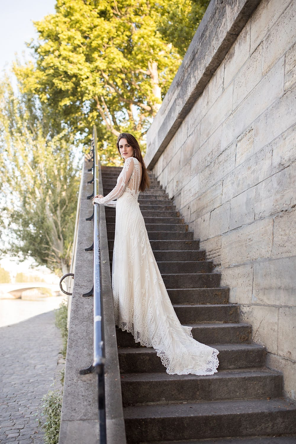 Model wearing Vinka Design Briar Wedding Dress, with gorgeous corded embroidered lace features, a sheer ivory base and long fitted sleeves with a gentle bell shape wrist. On steps in Paris