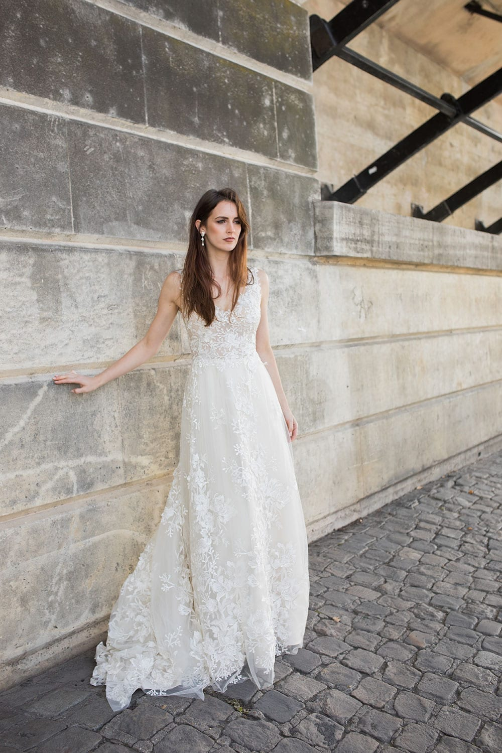 Model wearing Vinka Design Delta Wedding Dress, a Romantic v-neck wedding dress with a soft silhouette of layers of tulle & delicate 3D lace and sheer bodice on Parisian path