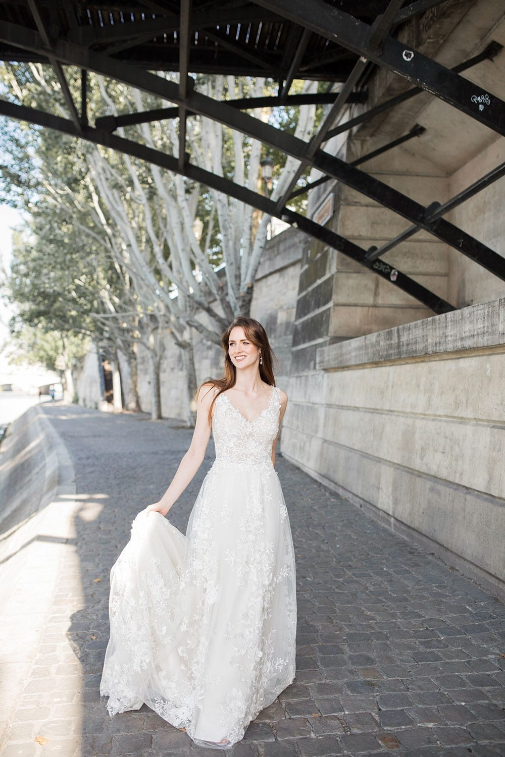 Model wearing Vinka Design Delta Wedding Dress, a Romantic v-neck wedding dress with a soft silhouette of layers of tulle & delicate 3D lace and sheer bodice on Parisian path under bridge.