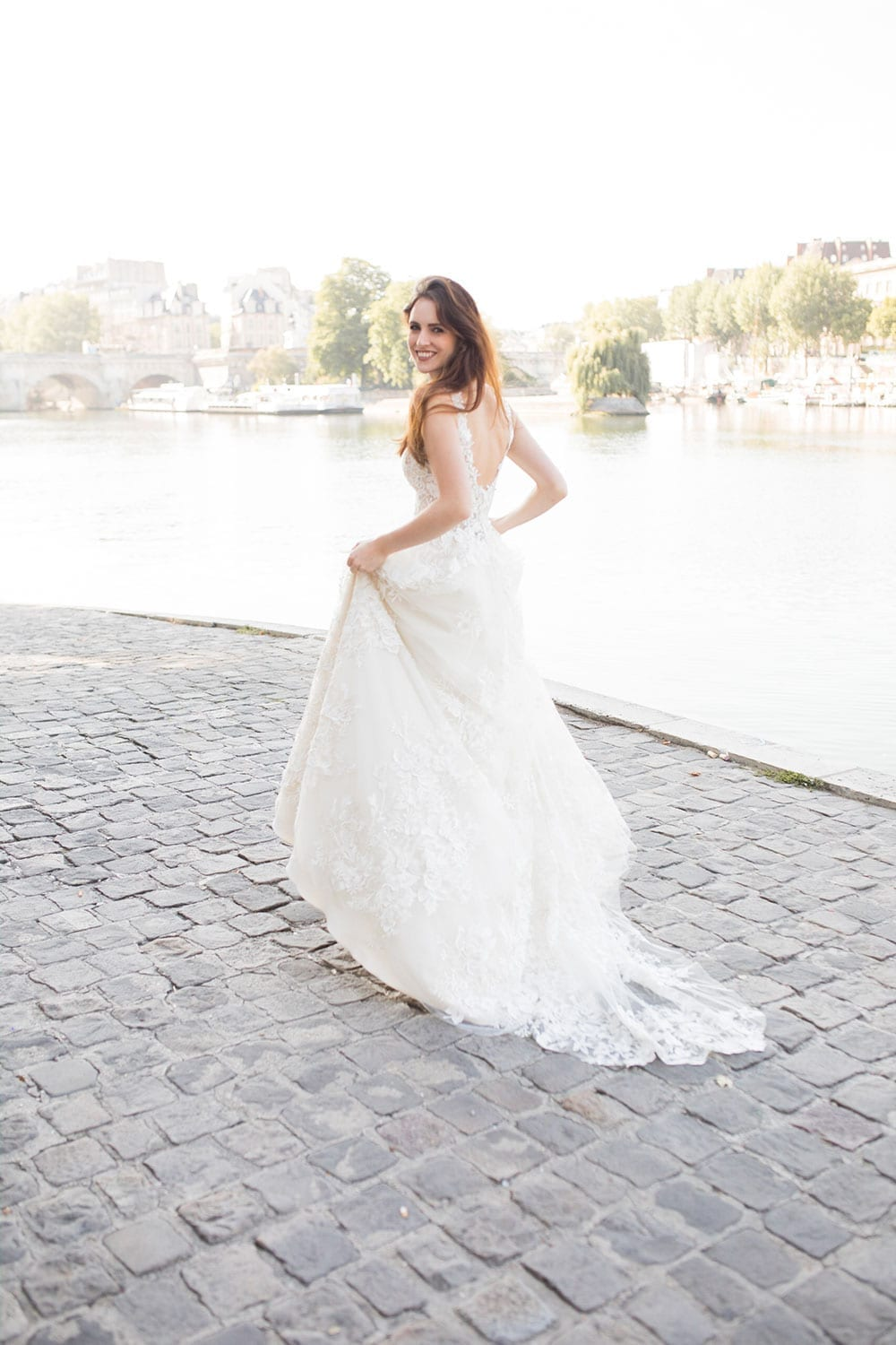 Model wearing Vinka Design Delta Wedding Dress, a Romantic v-neck wedding dress with a soft silhouette of layers of tulle & delicate 3D lace and sheer bodice on Parisian path walking along path next to river.