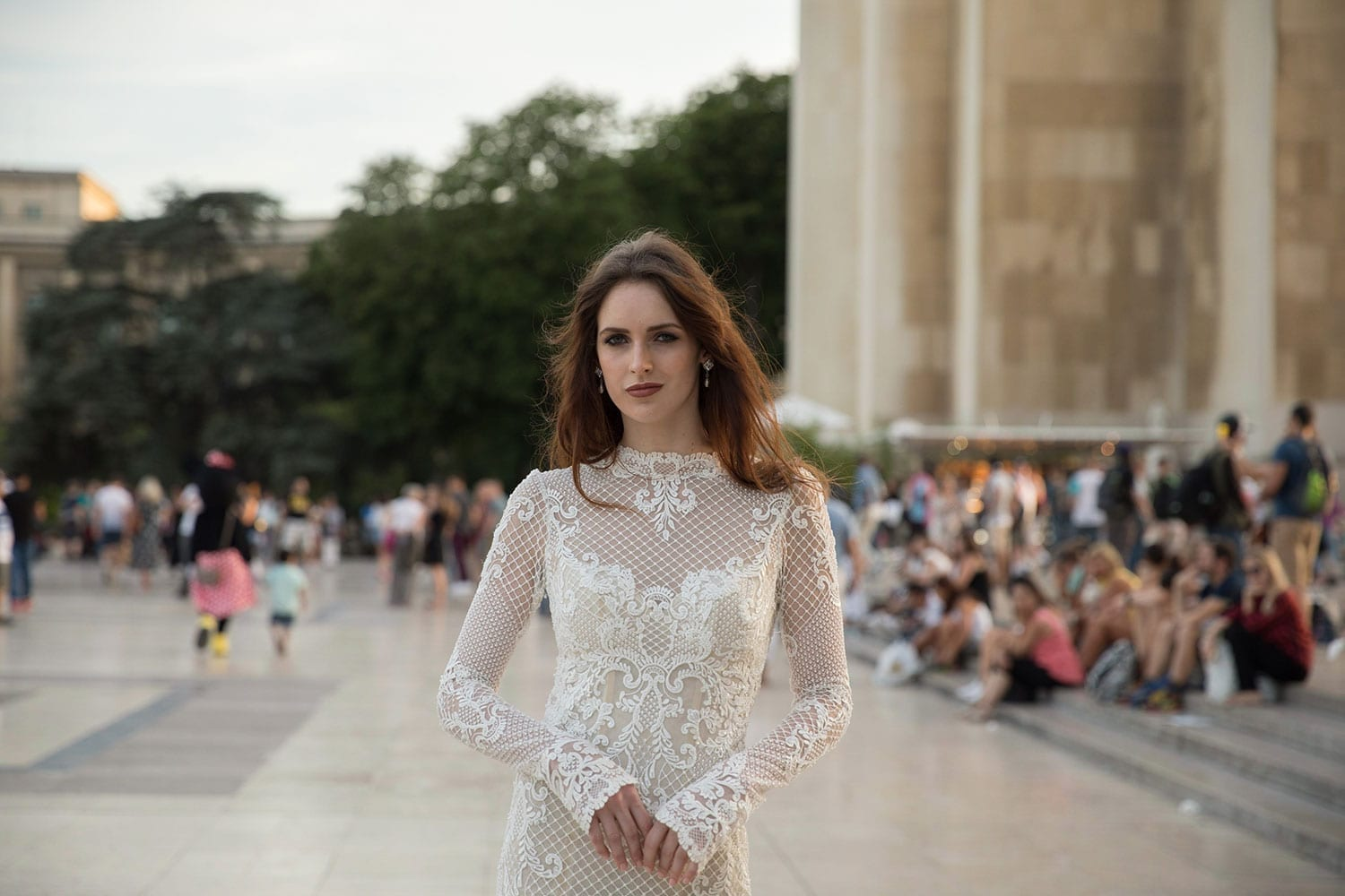 Model wearing Vinka Design Hayley Wedding Dress, a stunning fitted lace wedding dress with a divine low back, high neckline and fitted yet shaped sleeves. The lace is beautifully beaded and the gown is finished with little pearls. Parisian backdrop.