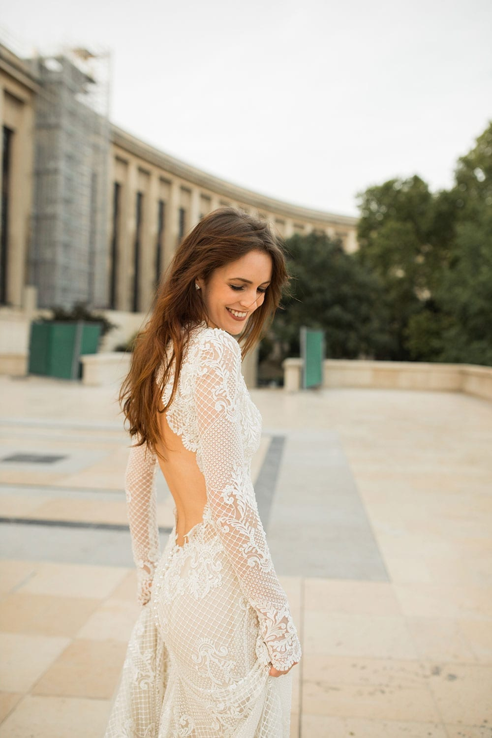 Model wearing Vinka Design Hayley Wedding Dress, a stunning fitted lace wedding dress with a divine low back, high neckline and fitted yet shaped sleeves. The lace is beautifully beaded and the gown is finished with little pearls. Parisian plaza and grand buildings in background.