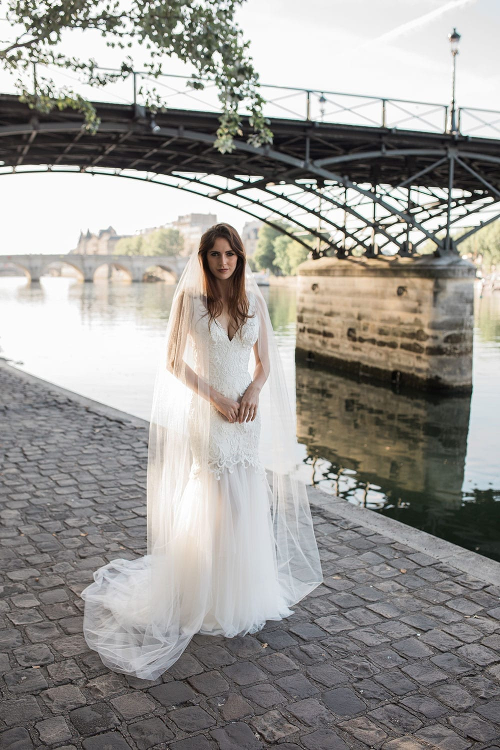 Model wearing Vinka Design Joanna Wedding Dress, a gorgeous wedding dress made with six different laces to create the beautiful bodice detail. The gown is a slim fit with a deep V neck and silk and tulle skirt. Worn next to river in Paris.