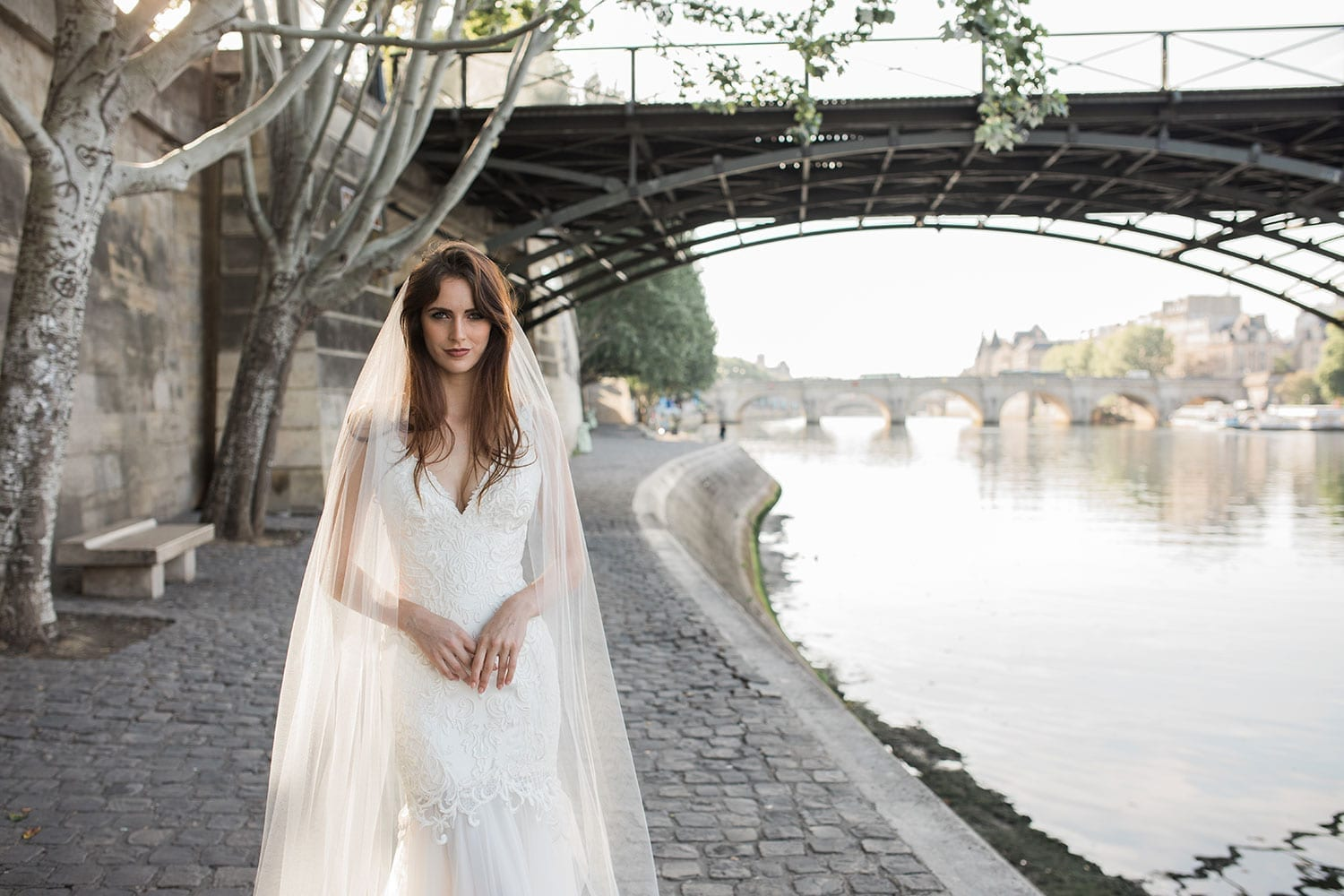 Model wearing Vinka Design Joanna Wedding Dress, a gorgeous wedding dress made with six different laces to create the beautiful bodice detail. The gown is a slim fit with a deep V neck and silk and tulle skirt. Worn in Paris with river and bridge in background.