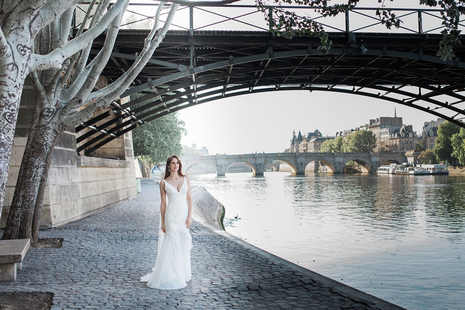 Model wearing Vinka Design Joanna Wedding Dress, a gorgeous wedding dress made with six different laces to create the beautiful bodice detail. The gown is a slim fit with a deep V neck and silk and tulle skirt. Worn next to river Seine in Paris.