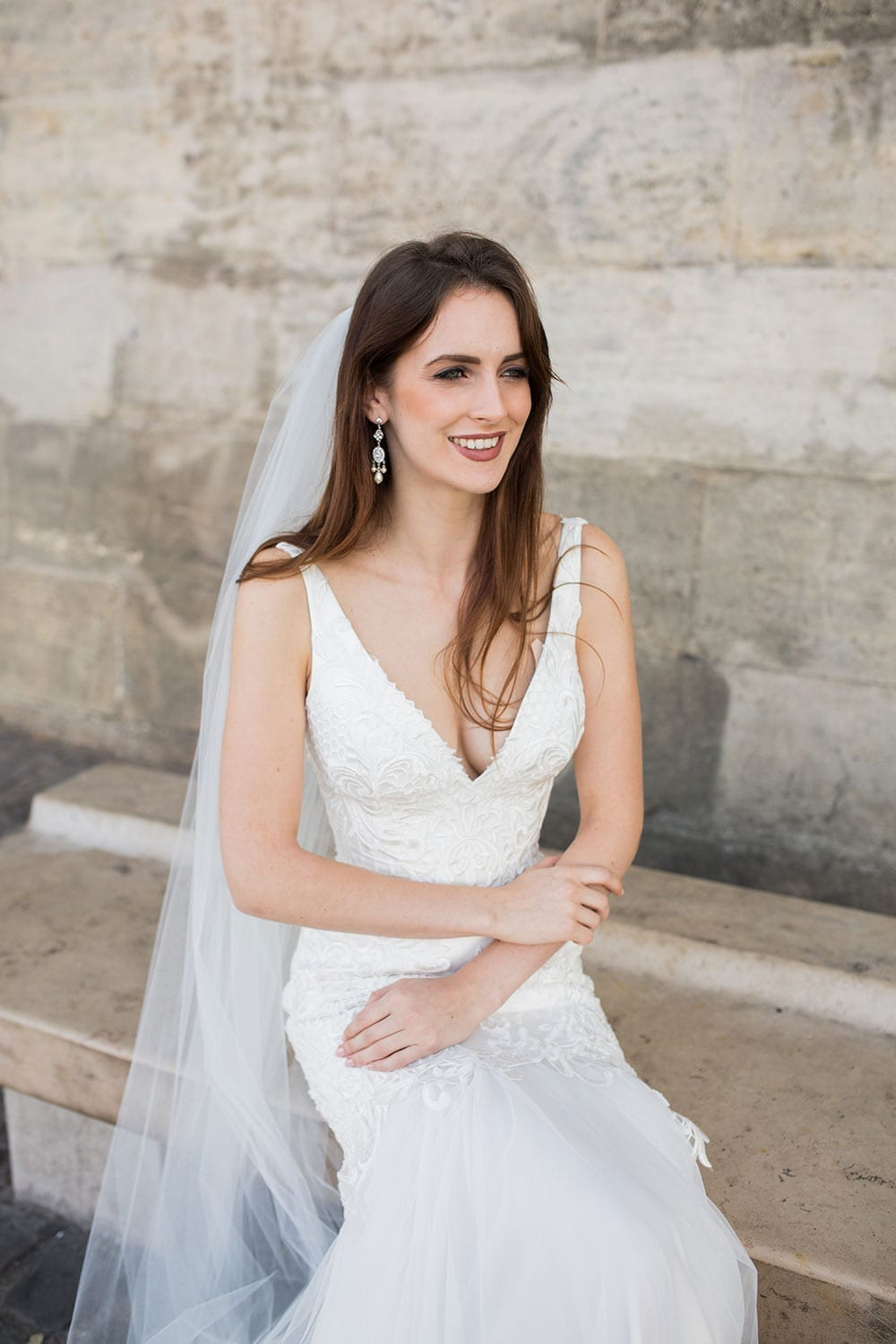 Model wearing Vinka Design Joanna Wedding Dress, a gorgeous wedding dress made with six different laces to create the beautiful bodice detail. The gown is a slim fit with a deep V neck and silk and tulle skirt. Worn seated in Paris.