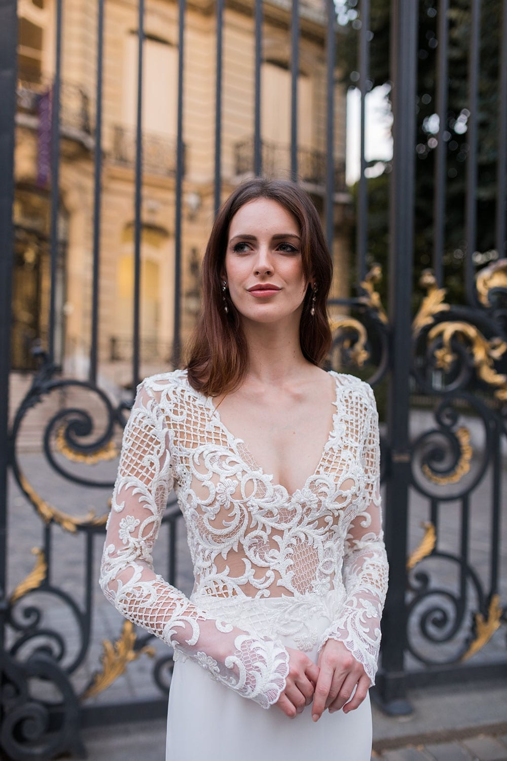 Model wearing Vinka Design Katrina Wedding Dress, a Stunning wedding dress sculptured with richly beaded lace . V neck gown with long fitted sleeves, a tailored skirt that fits softly over the hipline, and a beautiful train. Worn infront of gate in Paris.