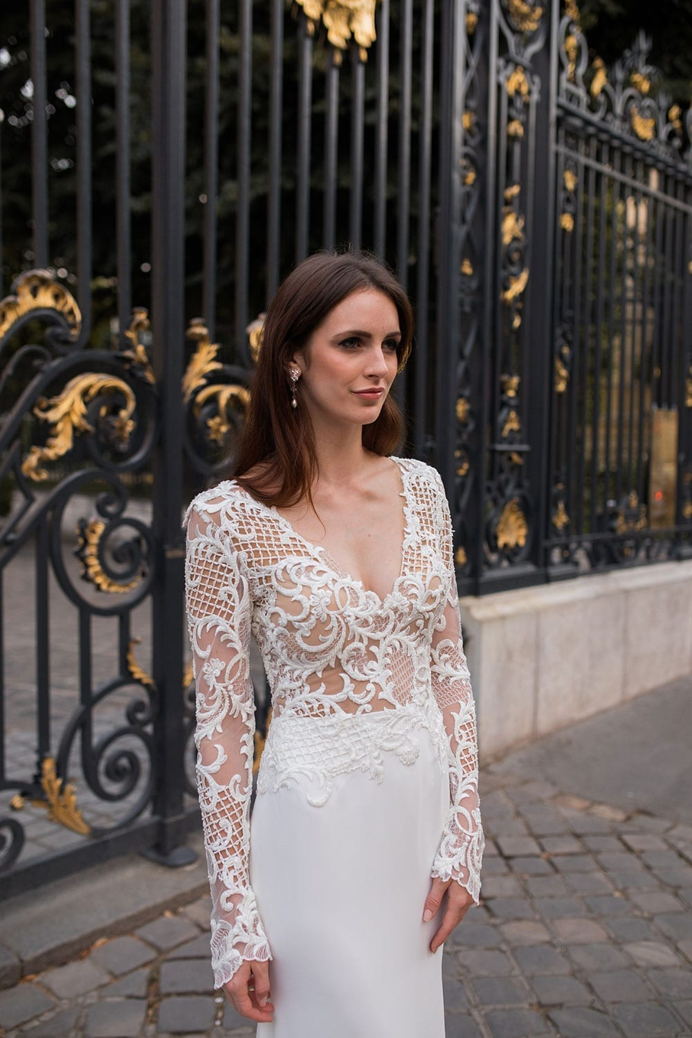Model wearing Vinka Design Katrina Wedding Dress, a Stunning wedding dress sculptured with richly beaded lace . V neck gown with long fitted sleeves, a tailored skirt that fits softly over the hipline, and a beautiful train. Worn infront of ornate gate in Paris.