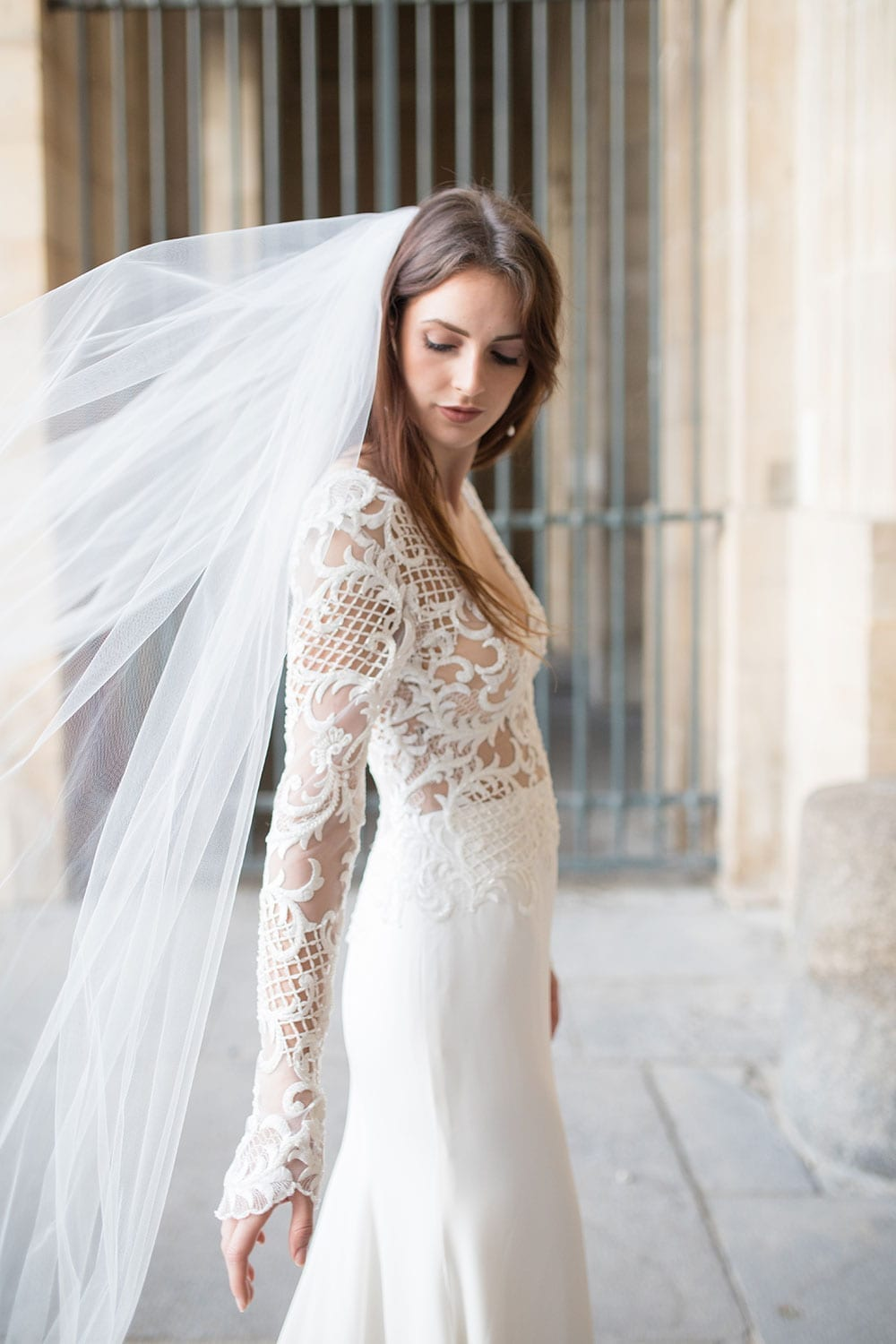 Model wearing Vinka Design Katrina Wedding Dress, a Stunning wedding dress sculptured with richly beaded lace . V neck gown with long fitted sleeves, a tailored skirt that fits softly over the hipline, and a beautiful train. Worn infront of ornate gate in Paris - side detail and custom veil.