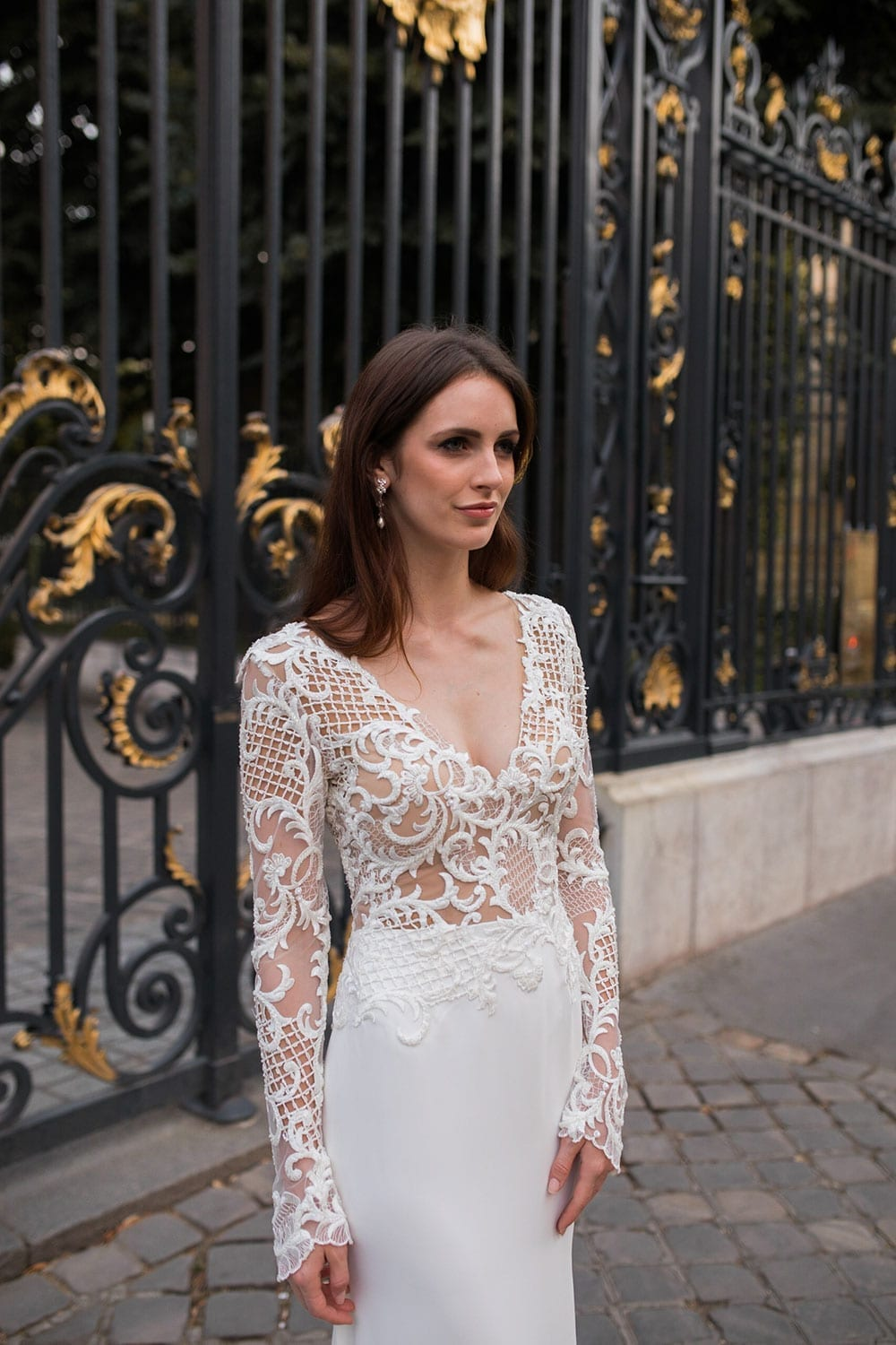Model wearing Vinka Design Katrina Wedding Dress, a Stunning wedding dress sculptured with richly beaded lace . V neck gown with long fitted sleeves, a tailored skirt that fits softly over the hipline, and a beautiful train. Worn infront of ornate gate in Paris - front detail.