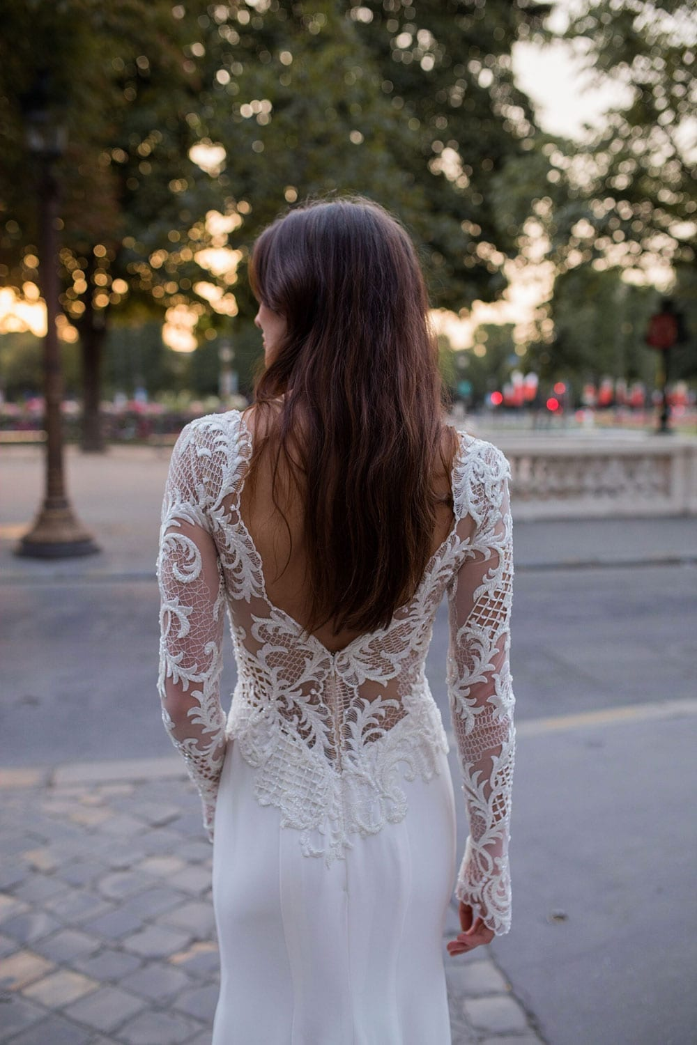 Model wearing Vinka Design Katrina Wedding Dress, a Stunning wedding dress sculptured with richly beaded lace . V neck gown with long fitted sleeves, a tailored skirt that fits softly over the hipline, and a beautiful train. Worn in Paris plaza - full back detail.