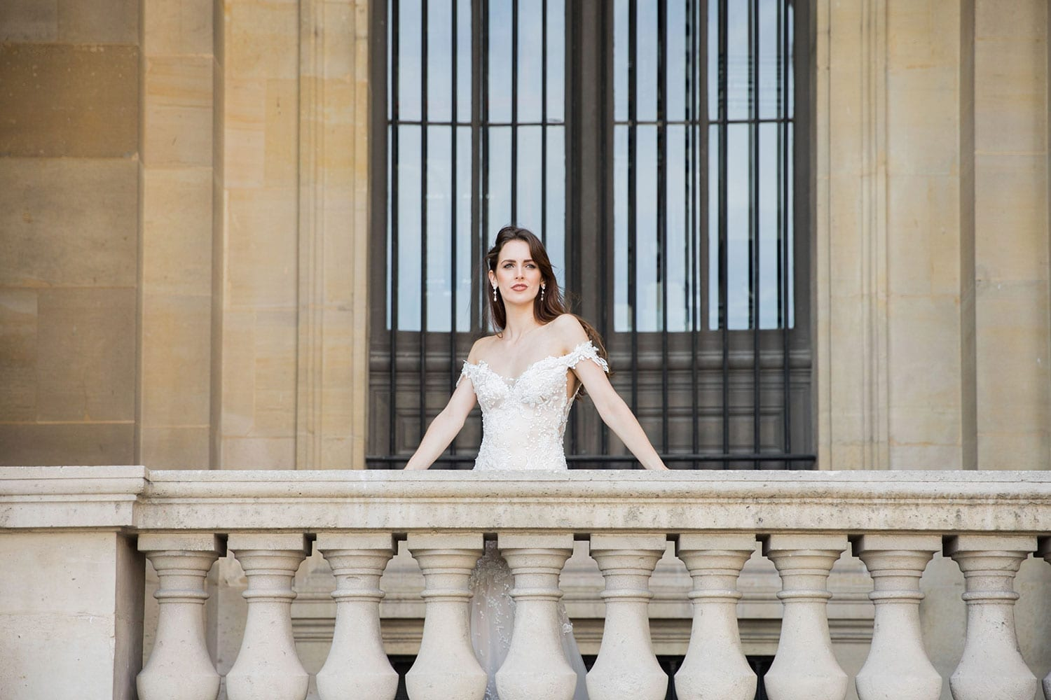 Model wearing Vinka Design Sashia Wedding Dress, an off-shoulder silk wedding dress with sheer lace back detail. This stunning gown features a fitted long line bodice and lace and soft tulle skirt. Worn on balcony in Paris.
