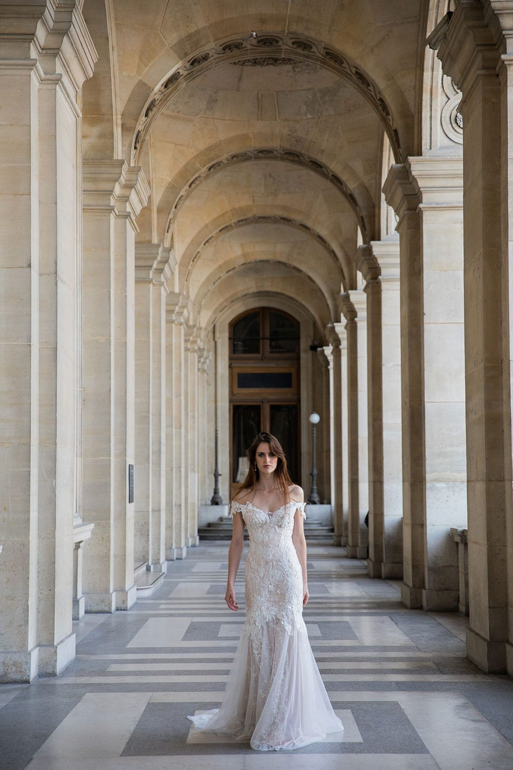Model wearing Vinka Design Sashia Wedding Dress, an off-shoulder silk wedding dress with sheer lace back detail. This stunning gown features a fitted long line bodice and lace and soft tulle skirt. Worn walking through high archways in old building, Paris.