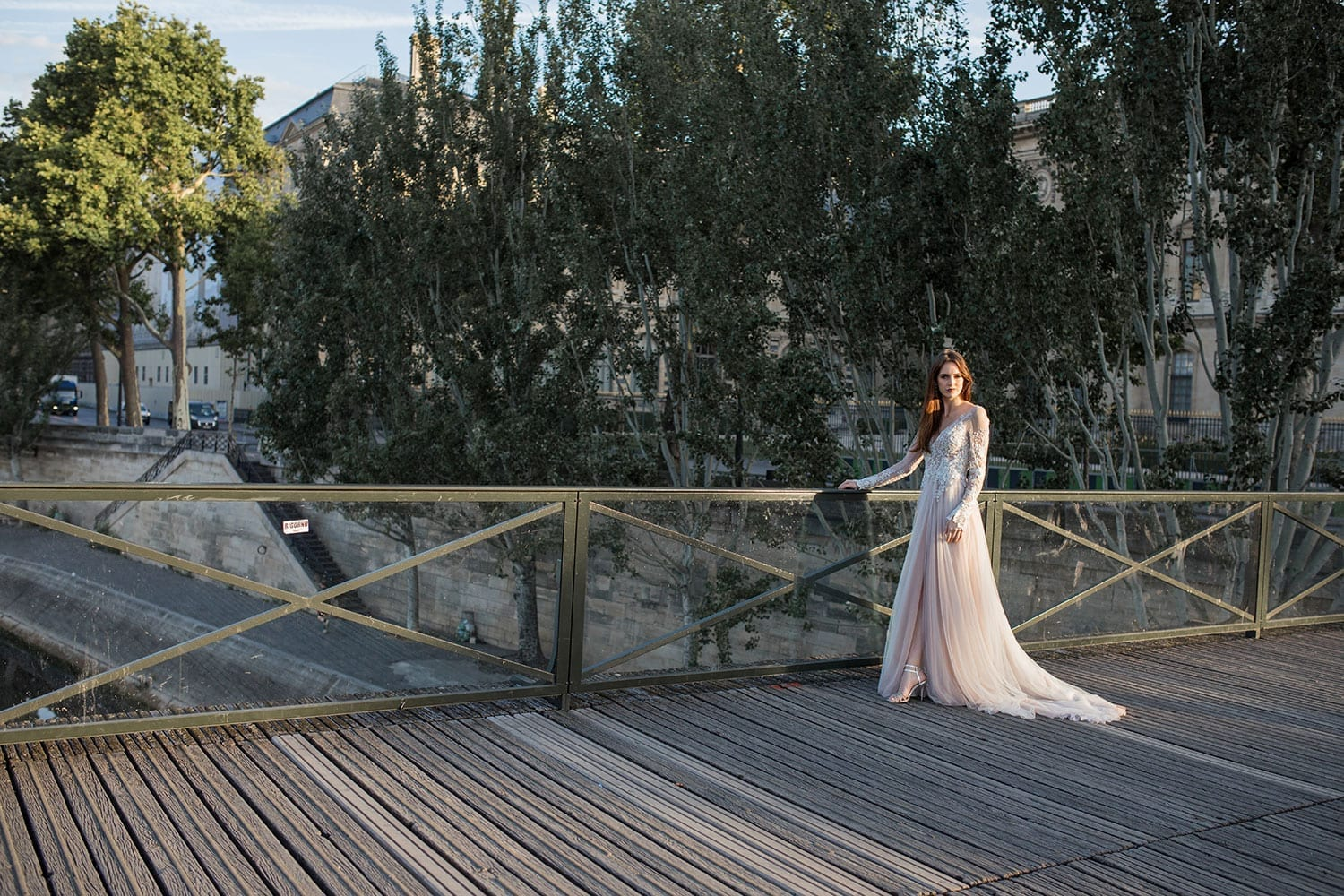 Model wearing Vinka Design Suri Wedding Dress, a stunning silver beaded lace wedding dress with sheer long sleeves and no back. The skirt is made with layers of dreamy tulle and silk with a side front split. Worn on boardwalk in Paris.