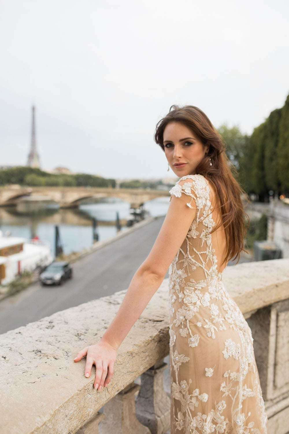 Model wearing Vinka Design Vianna Wedding Dress, a dreamy wedding dress with richly beaded embroidery on a nude base, a slightly sheer skirt and elegant train. Gorgeous low back, little cap sleeves and front v-neckline. Worn on bridge in Paris.