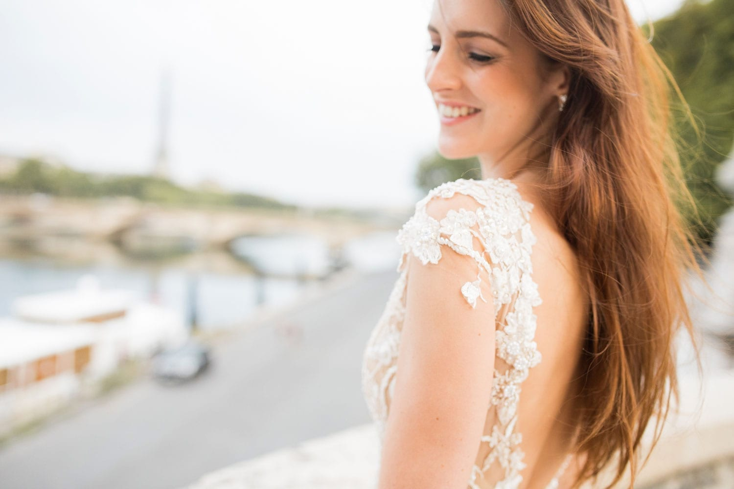 Model wearing Vinka Design Vianna Wedding Dress, a dreamy wedding dress with richly beaded embroidery on a nude base, a slightly sheer skirt and elegant train. Gorgeous low back, little cap sleeves and front v-neckline. Close up of detail worn on bridge in Paris.