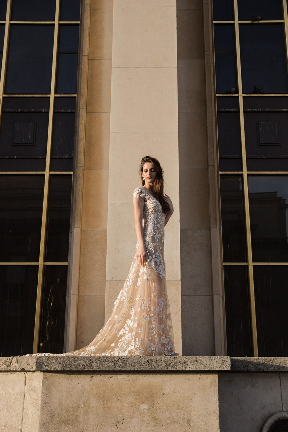 Model wearing Vinka Design Vianna Wedding Dress, a dreamy wedding dress with richly beaded embroidery on a nude base, a slightly sheer skirt and elegant train. Gorgeous low back, little cap sleeves and front v-neckline. full length in front of large column in Paris.
