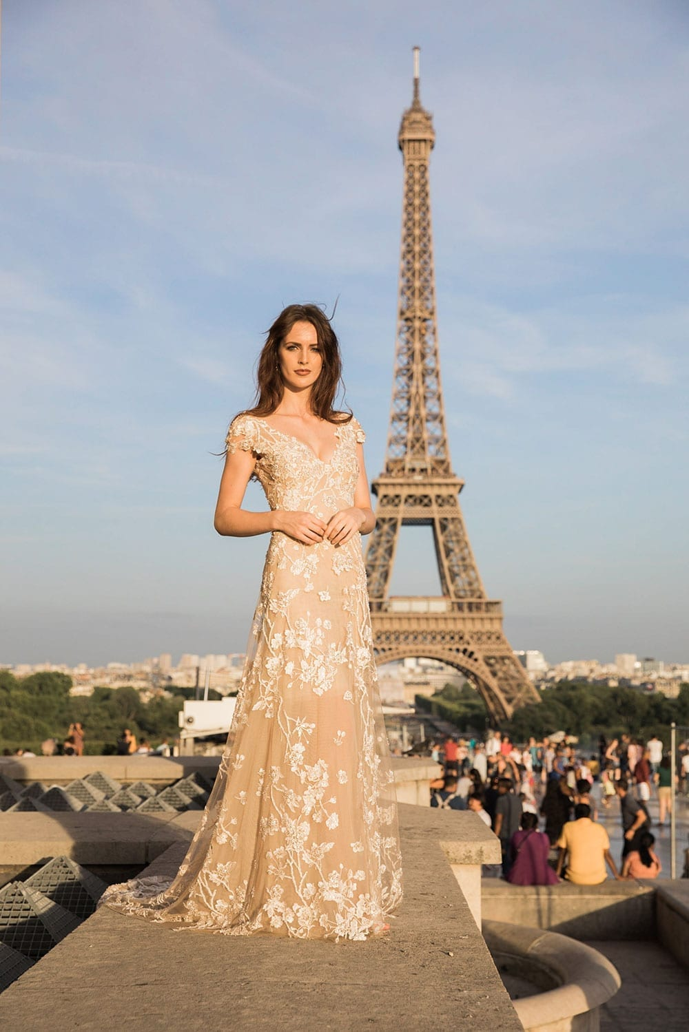 Model wearing Vinka Design Vianna Wedding Dress, a dreamy wedding dress with richly beaded embroidery on a nude base, a slightly sheer skirt and elegant train. Gorgeous low back, little cap sleeves and front v-neckline. Worn in Paris in front of Eiffel Tower - full length.