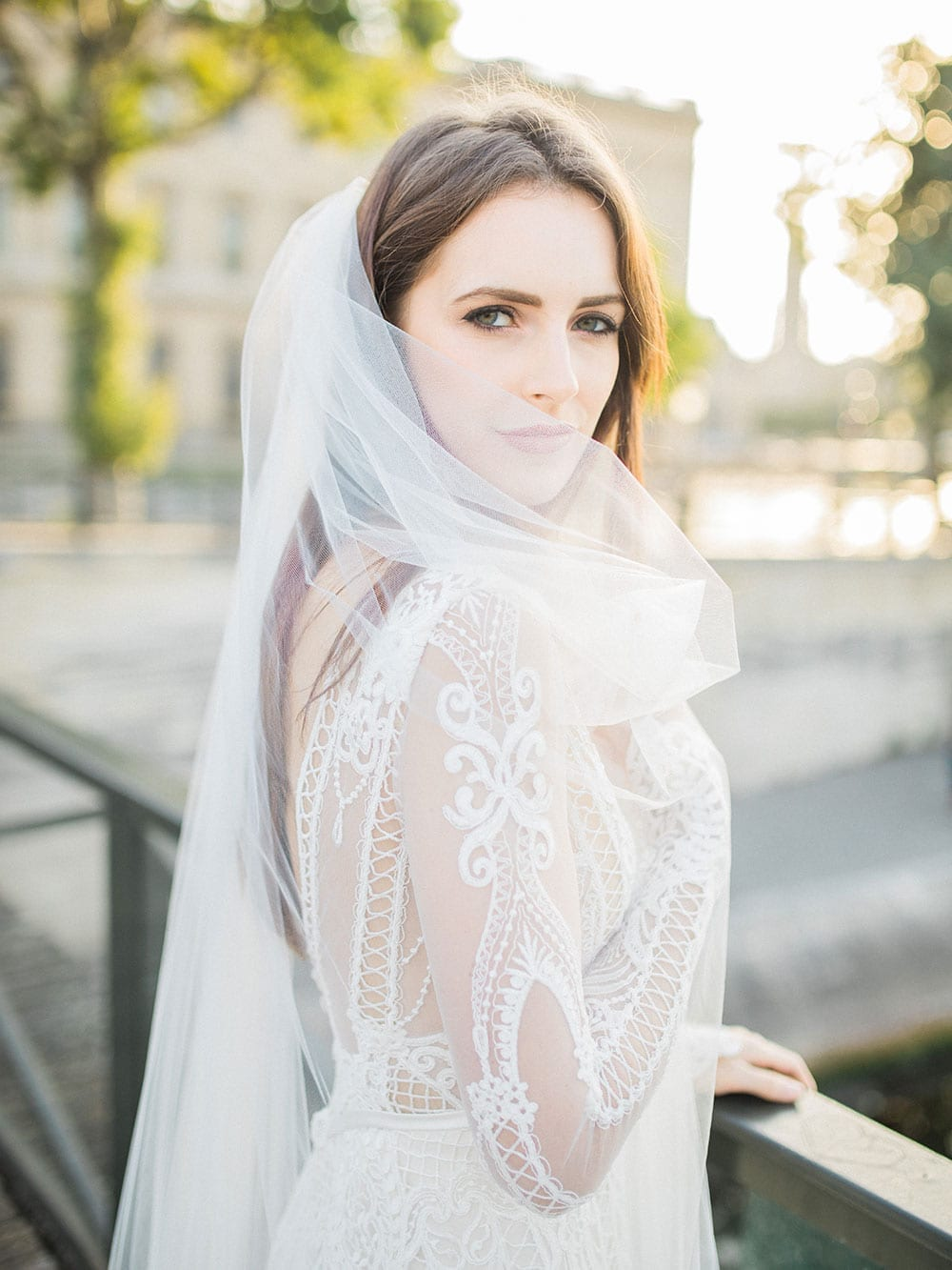 Model wearing Vinka Design Briar Wedding Dress, an Embroidered Lace Wedding Gown in Paris close up with veil