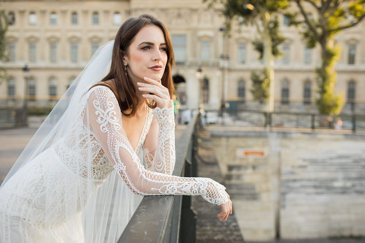 Model wearing Vinka Design Briar Wedding Dress, an Embroidered Lace Wedding Gown in Paris close up leaning on wall