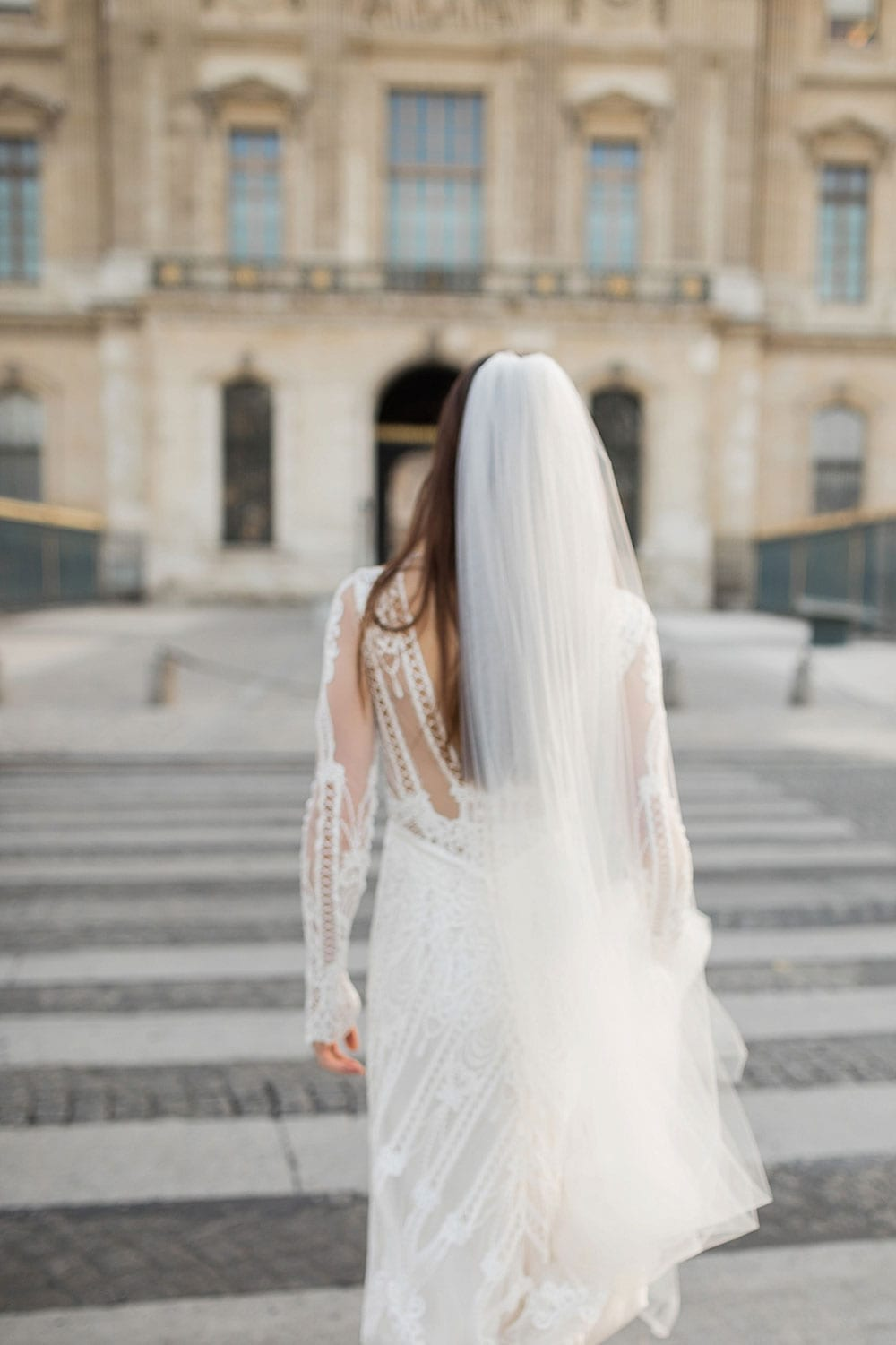 Model wearing Vinka Design Briar Wedding Dress, an Embroidered Lace Wedding Gown in Paris walking away