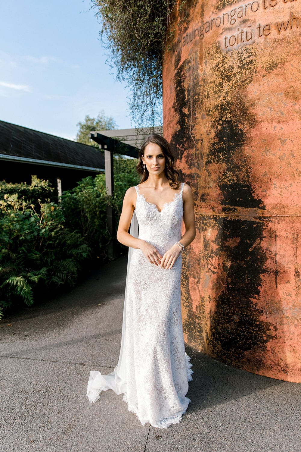 Model wearing Vinka Design Arabella Wedding Dress, a Beaded Lace Wedding Gown with Cape in Hamilton Gardens portrait