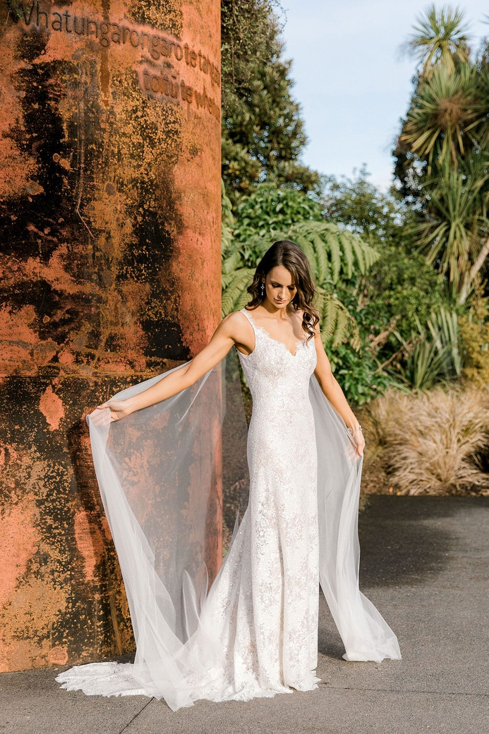 Model wearing Vinka Design Arabella Wedding Dress, a Beaded Lace Wedding Gown with Cape in Hamilton Gardens arms stretched displaying cape