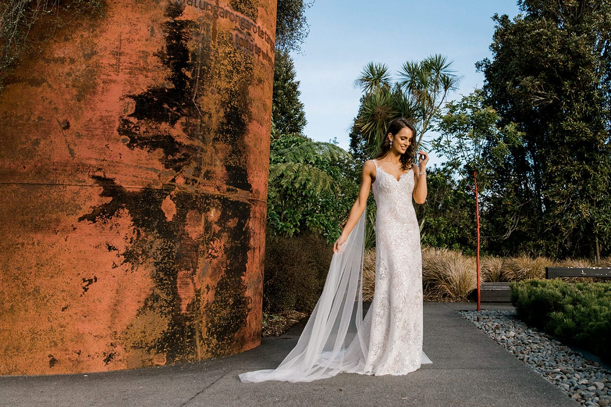 Model wearing Vinka Design Arabella Wedding Dress, a Beaded Lace Wedding Gown with Cape in Hamilton Gardens