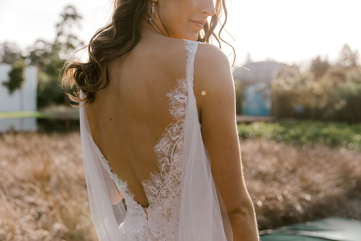 Model wearing Vinka Design Arabella Wedding Dress, a Beaded Lace Wedding Gown with Cape in Hamilton Gardens close up of back detail