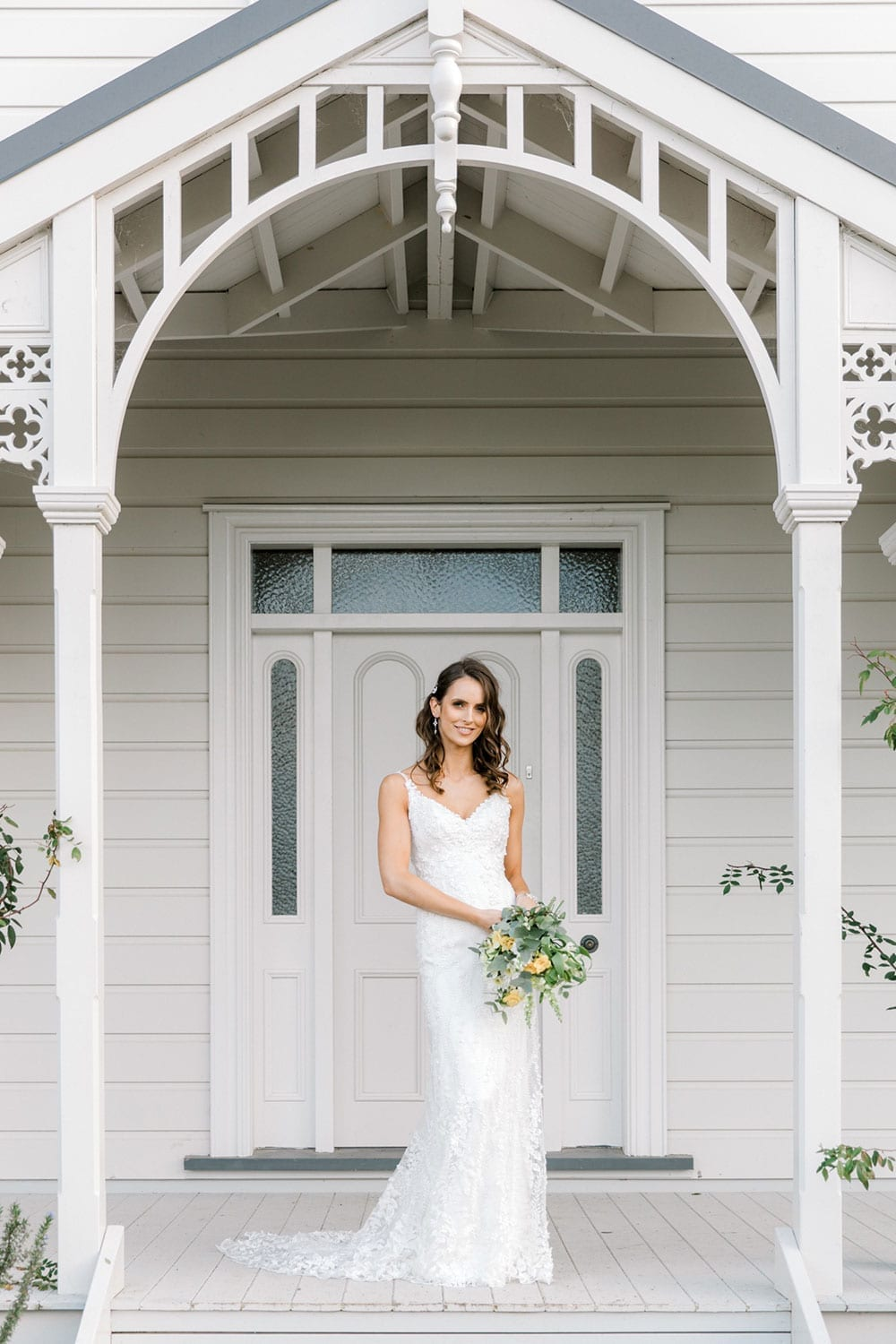 Model wearing Vinka Design Camille Wedding Dress, a Timeless Fitted Wedding Gown on the veranda of a beautiful New Zealand home holding a bouquet