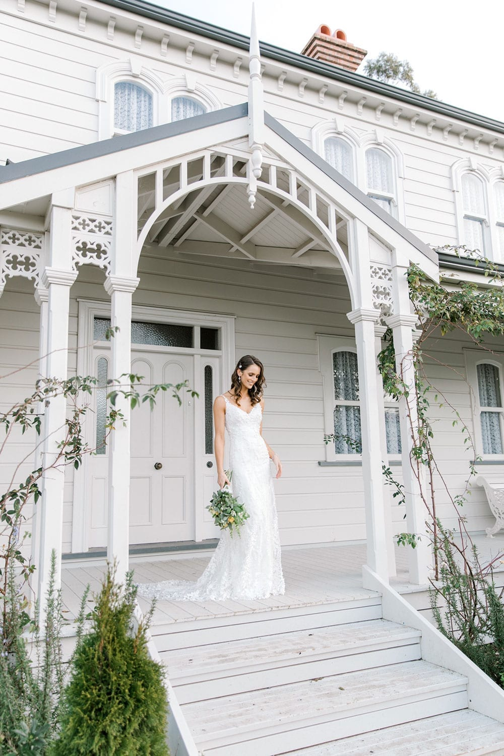 Model wearing Vinka Design Camille Wedding Dress, a Timeless Fitted Wedding Gown on the veranda of a wooden building with an arch