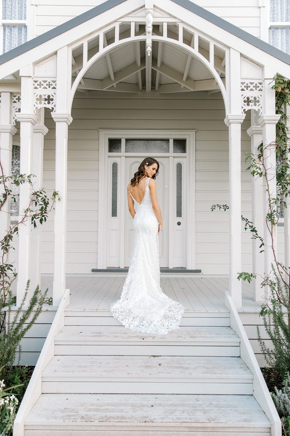 Model wearing Vinka Design Camille Wedding Dress, a Timeless Fitted Wedding Gown on the veranda of a wooden building with an arch facing away displaying train