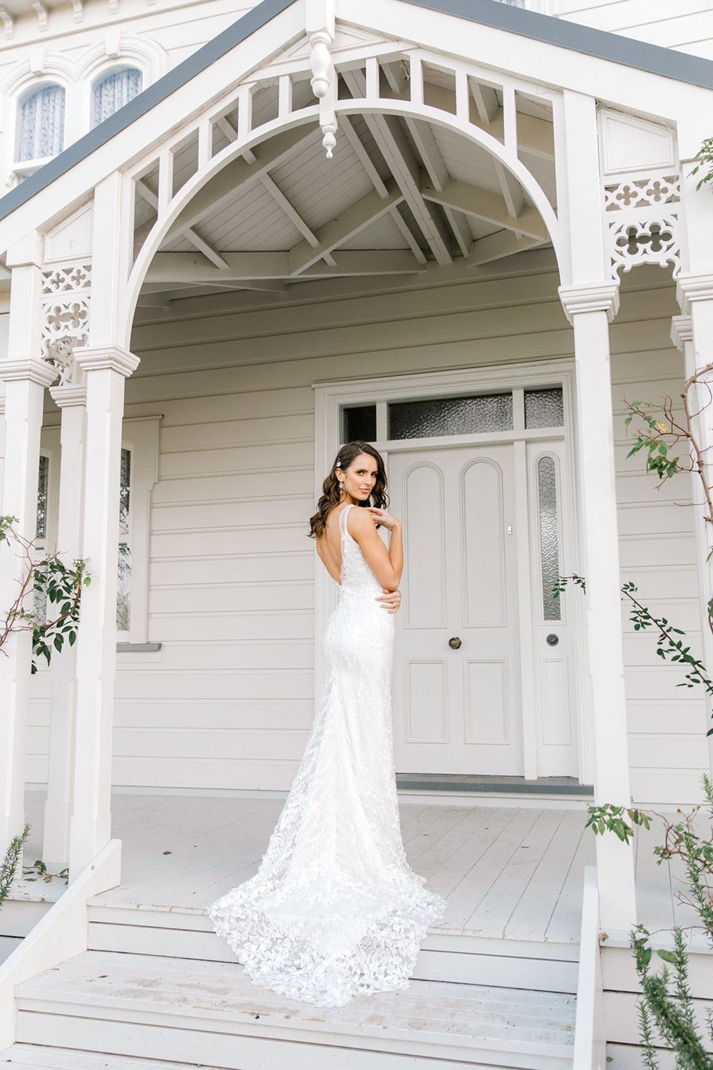 Model wearing Vinka Design Camille Wedding Dress, a Timeless Fitted Wedding Gown on the veranda of a wooden building with an arch facing away train displayed