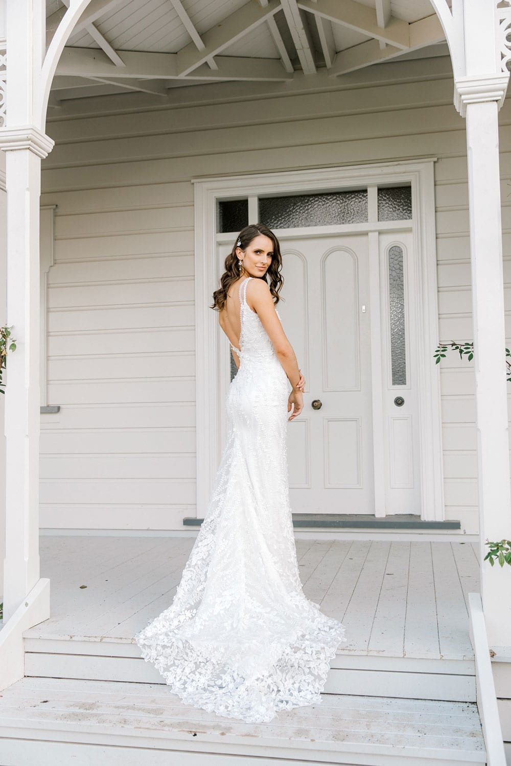 Model wearing Vinka Design Camille Wedding Dress, a Timeless Fitted Wedding Gown on the veranda of a wooden building with an arch facing away showing low back on dress
