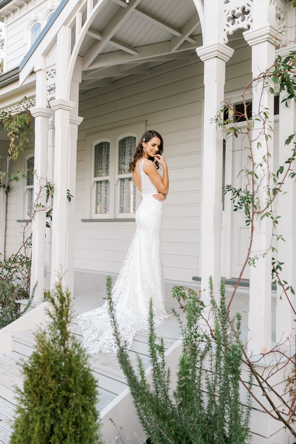 Model wearing Vinka Design Camille Wedding Dress, a Timeless Fitted Wedding Gown on the veranda of a wooden building with an arch facing away showing low back on dress through garden