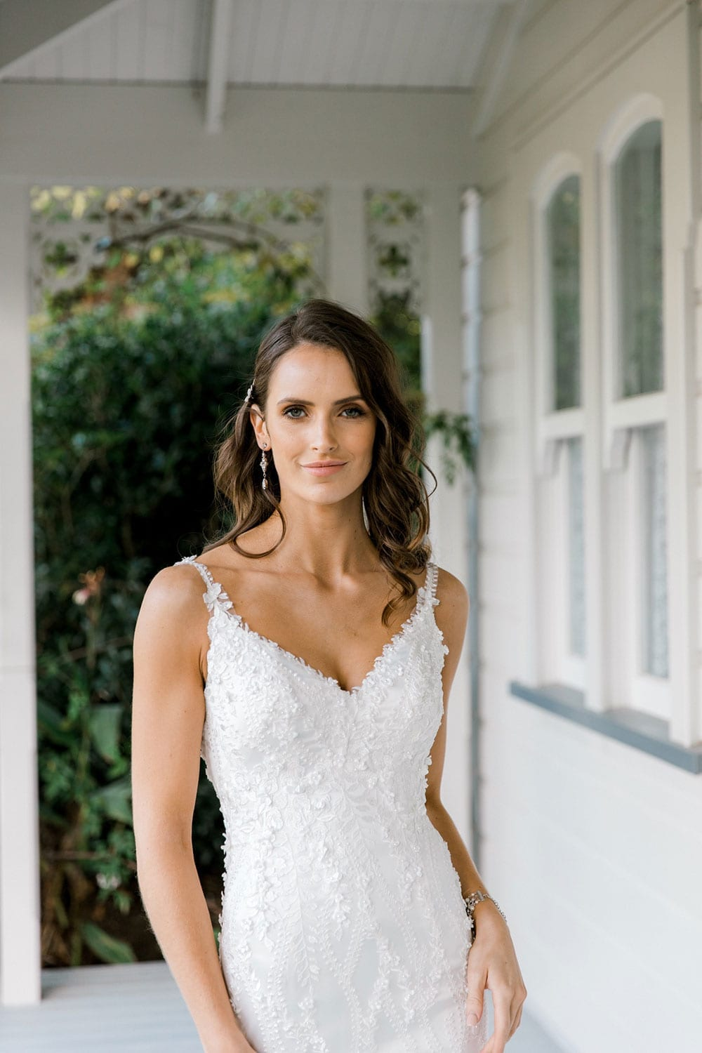Model wearing Vinka Design Camille Wedding Dress, a Timeless Fitted Wedding Gown on the veranda of a beautiful New Zealand home