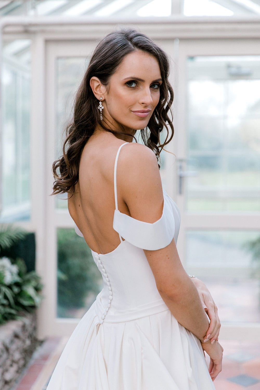 Model wearing Vinka Design Chiara Wedding Dress, a Modern Silk Wedding Gown with Train in a botanical garden greenhouse close up looking over shoulder