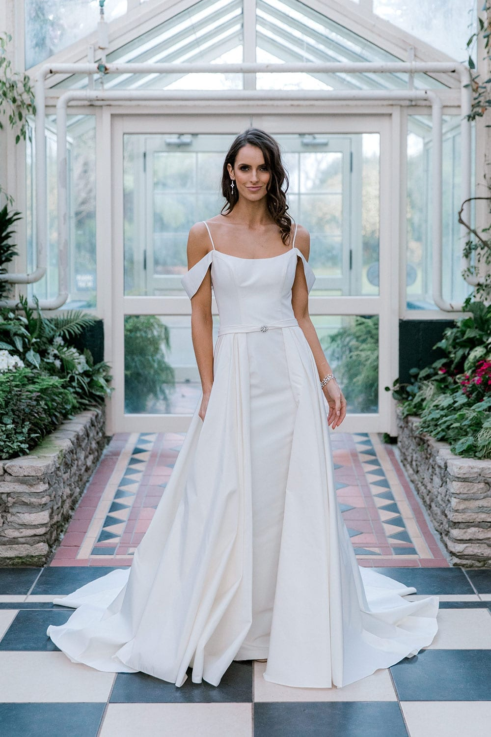 Model wearing Vinka Design Chiara Wedding Dress, a Modern Silk Wedding Gown with Train in a botanical garden greenhouse portrait
