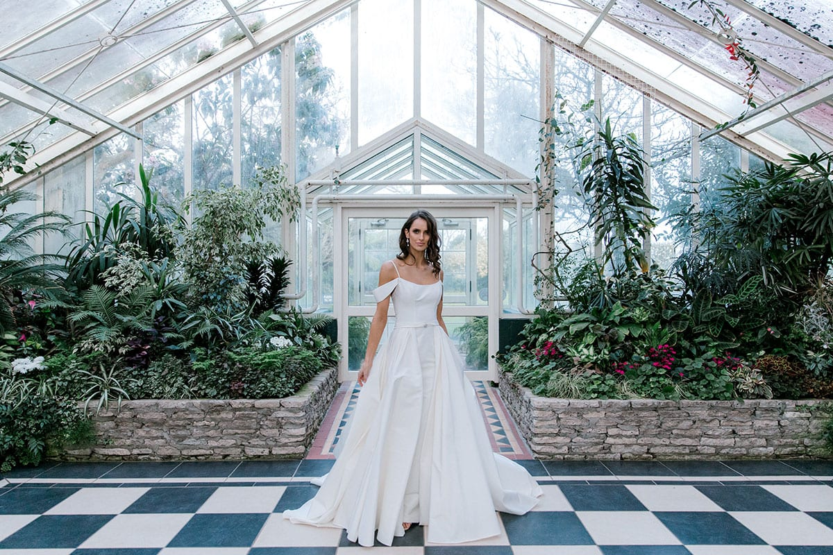 Model wearing Vinka Design Chiara Wedding Dress, a Modern Silk Wedding Gown with Train in a botanical garden greenhouse landscape