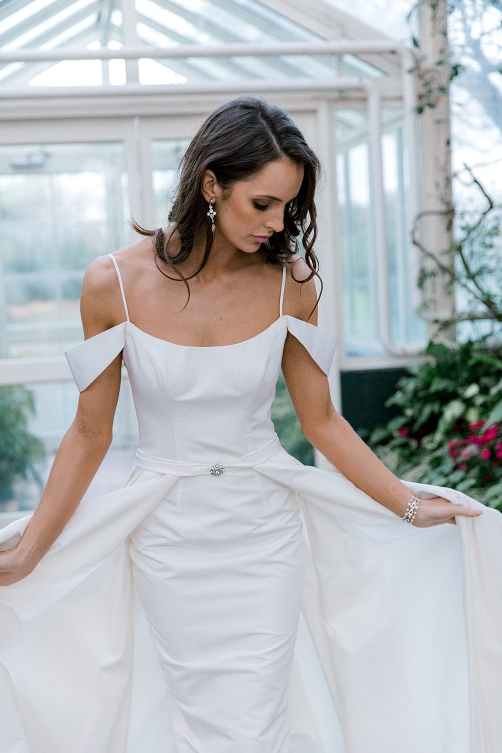 Model wearing Vinka Design Chiara Wedding Dress, a Modern Silk Wedding Gown with Train in a botanical garden greenhouse close up flaring out train