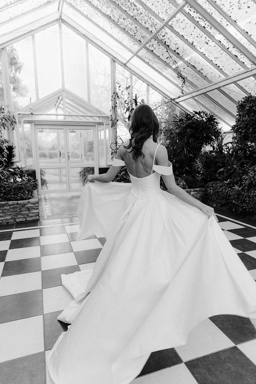 Model wearing Vinka Design Chiara Wedding Dress, a Modern Silk Wedding Gown with Train in a botanical garden greenhouse facing away with train displayed in black and white