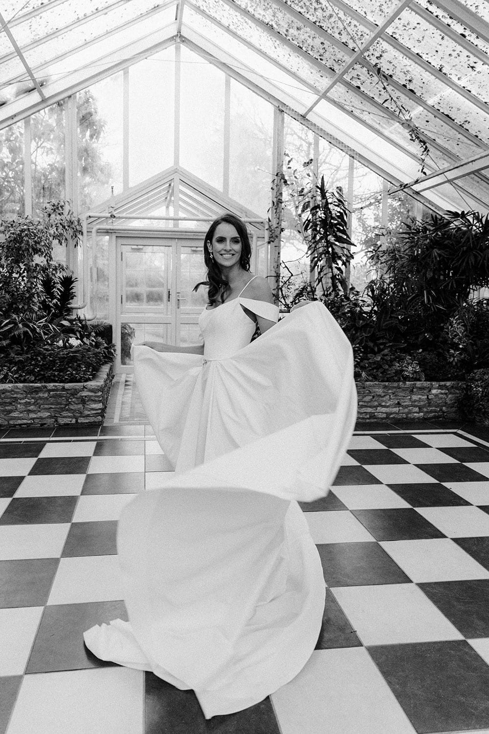 Model wearing Vinka Design Chiara Wedding Dress, a Modern Silk Wedding Gown with Train in a botanical garden greenhouse with train displayed in black and white