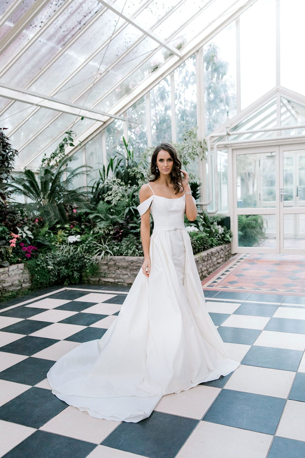 Model wearing Vinka Design Chiara Wedding Dress, a Modern Silk Wedding Gown with Train in a botanical garden greenhouse train to the side