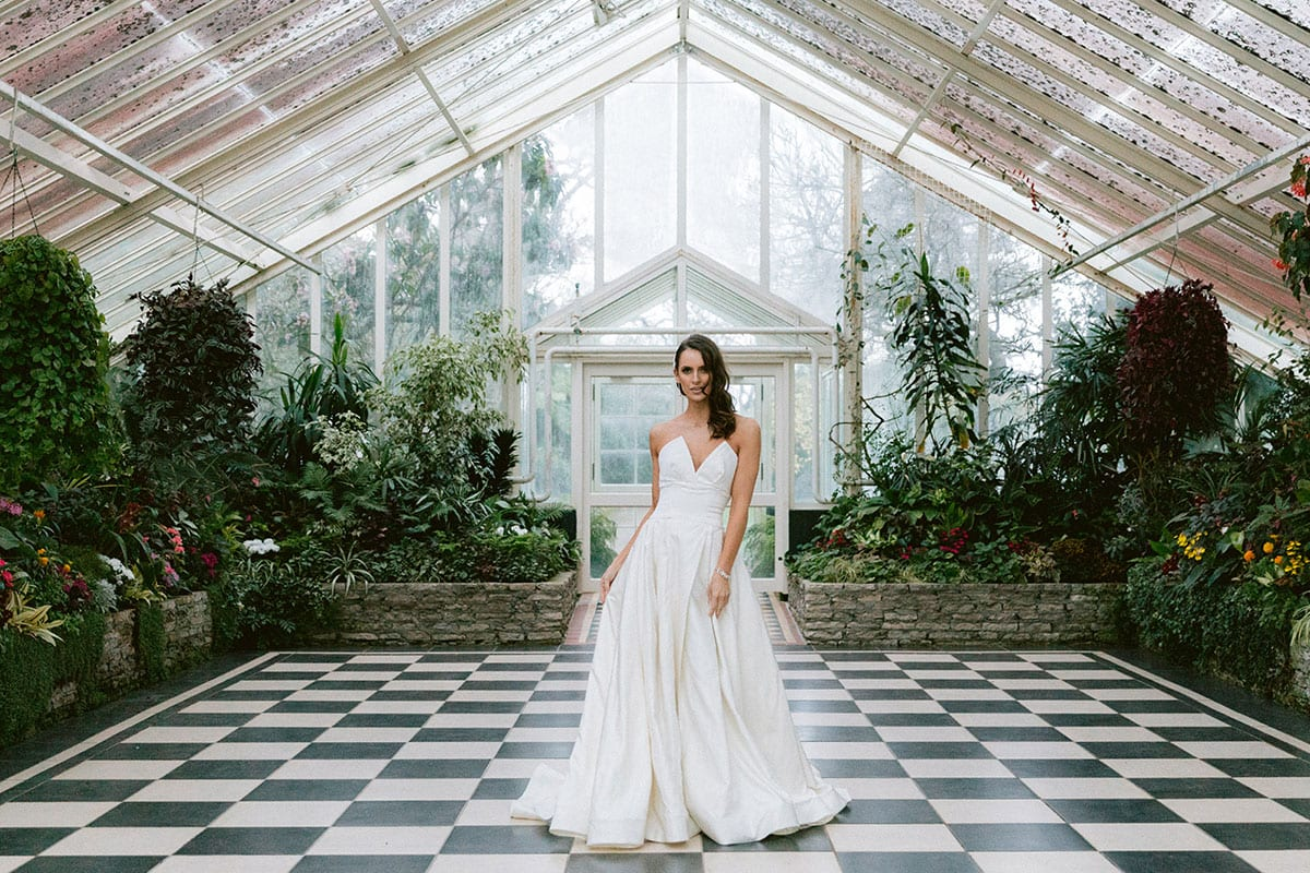 Model wearing Vinka Design Germaine Wedding Dress, a strapless dramatic wedding dress with split in a botanical garden greenhouse landscape