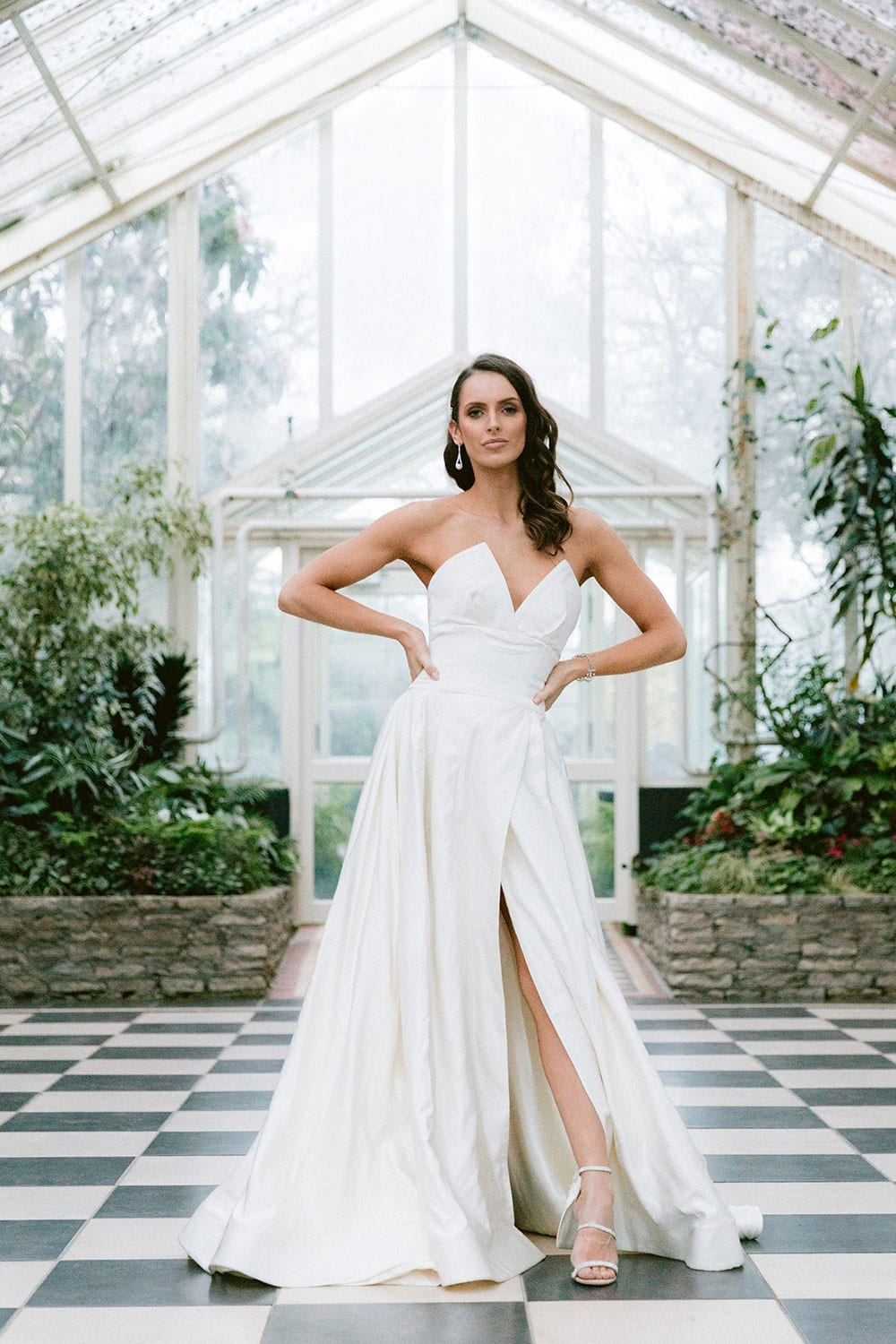 Model wearing Vinka Design Germaine Wedding Dress, a strapless dramatic wedding dress with split in a botanical garden greenhouse