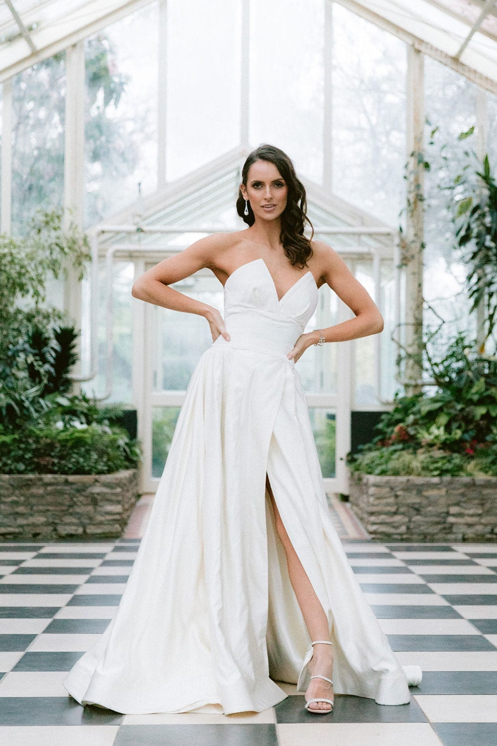 Model wearing Vinka Design Germaine Wedding Dress, a strapless dramatic wedding dress with split in a botanical garden greenhouse hands on hips