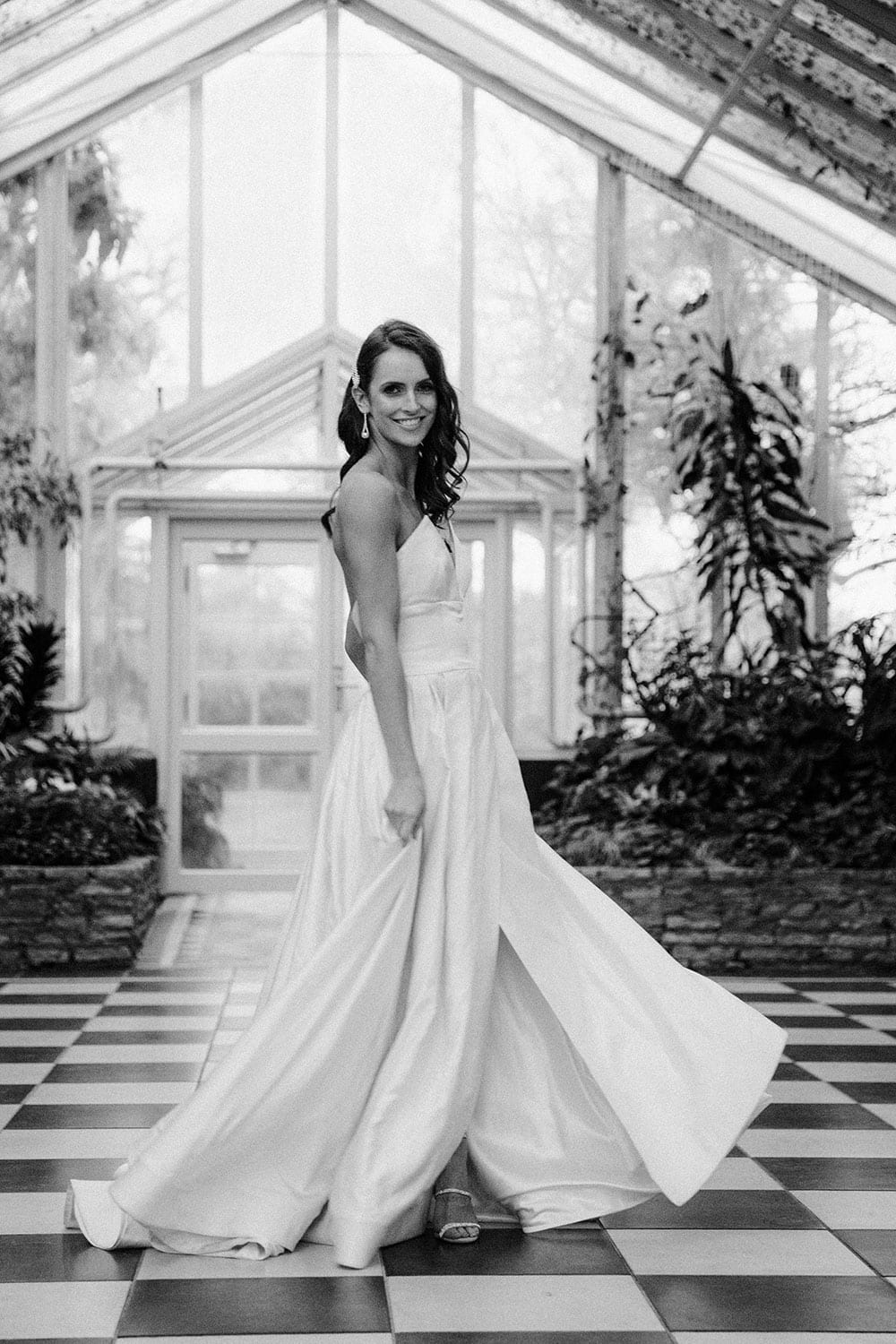 Model wearing Vinka Design Germaine Wedding Dress, a strapless dramatic wedding dress with split in a botanical garden greenhouse black and white