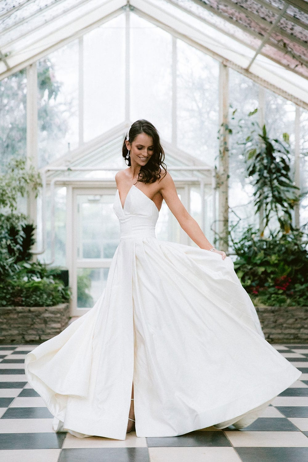 Model wearing Vinka Design Germaine Wedding Dress, a strapless dramatic wedding dress with split in a botanical garden greenhouse holding skirt out