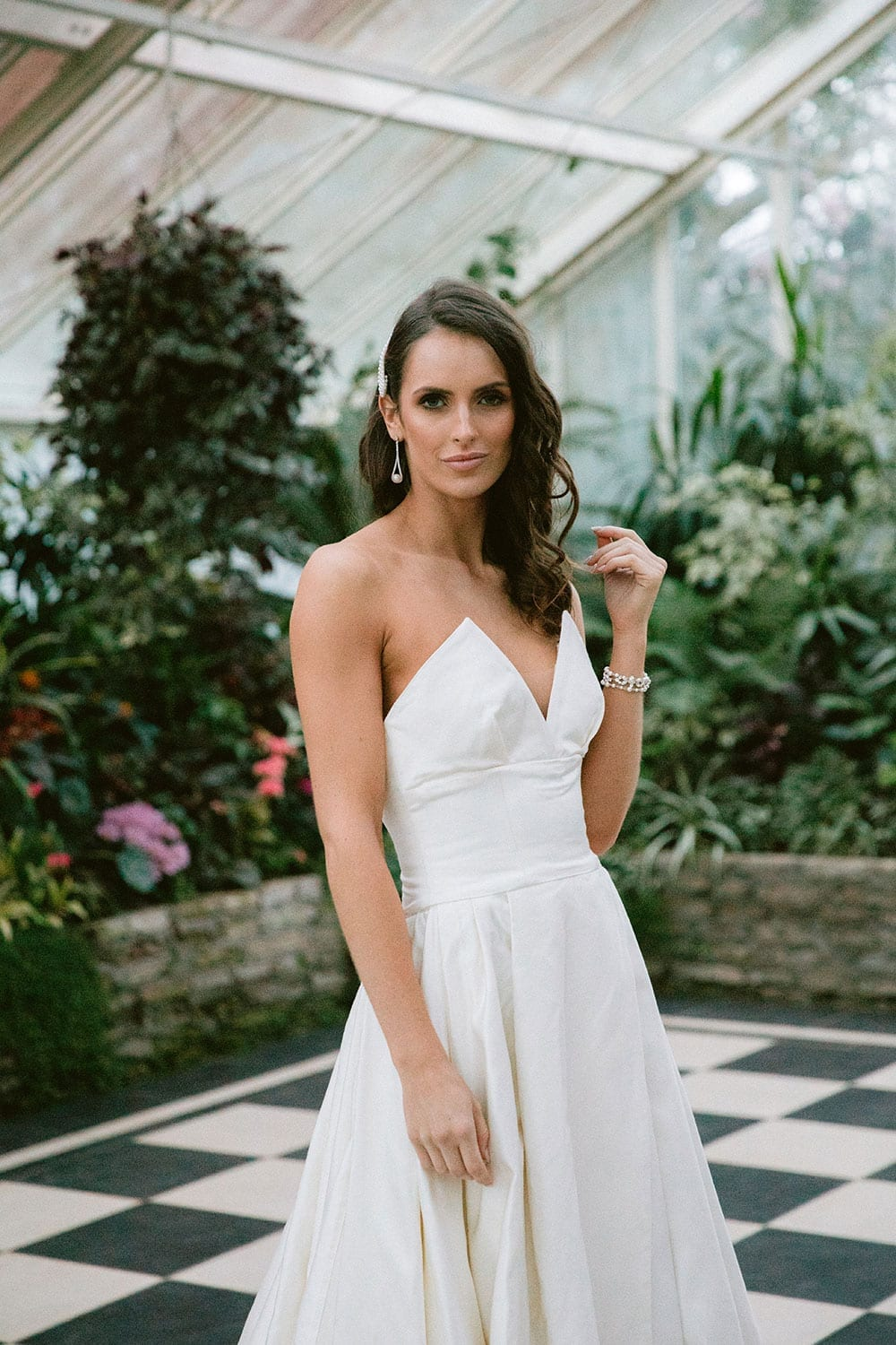 Model wearing Vinka Design Germaine Wedding Dress, a strapless dramatic wedding dress with split in a botanical garden greenhouse close up of top half
